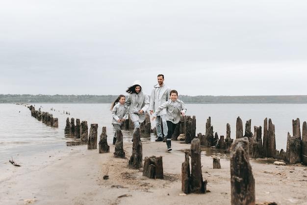 家族が走っていて、レインコートの海の近くで楽しむ
