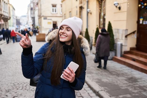 冬時間で街の通りを歩いてファッショナブルな少女の肖像画