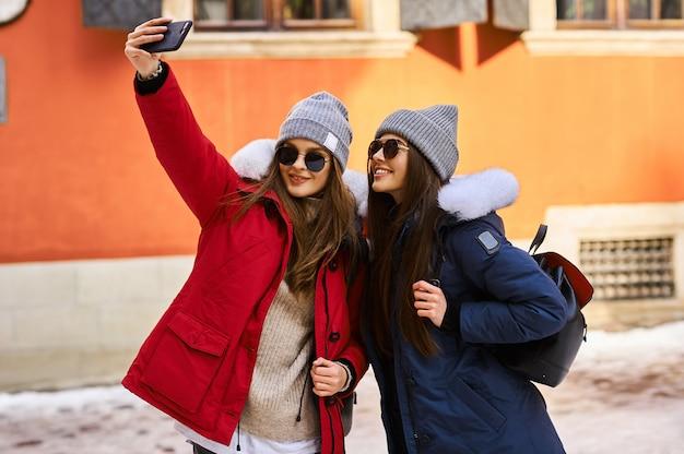 トレンディな若い女の子がクリスマスタイムに街に飛び込んで楽しんで