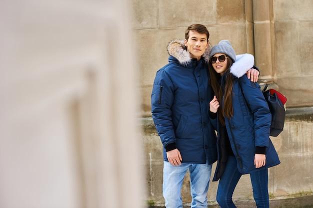 トレンディな若いカップルはクリスマスに街を歩く