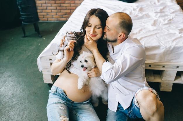 妊娠中のカップルは、赤ちゃんを待って、抱きしめるベッドでうそをつく