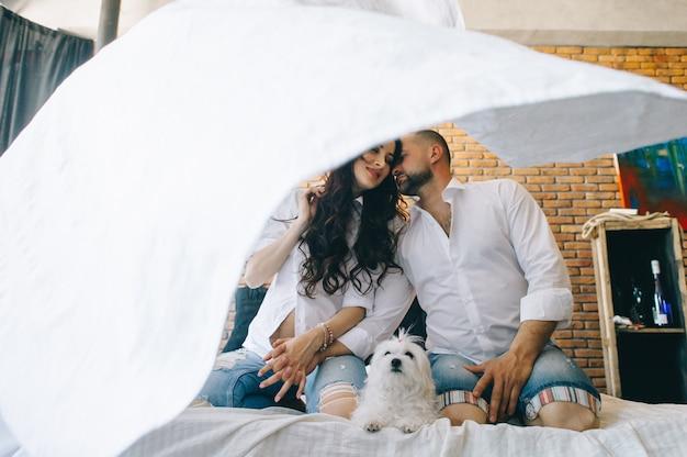 Влюбленная пара беременных лежат в постели, обнимаются, ожидая ребенка