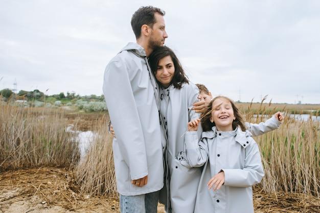 湖の近くのレインコートに身を包んだ美しい家族の肖像画