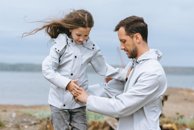 お父さんと娘の海の近くのレインコートの家族の肖像画