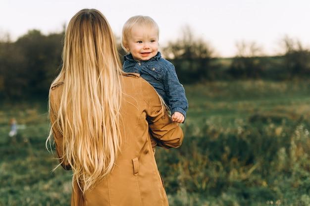 Портрет матери и ее сына работает в поле на закате