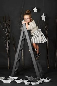 Фанни маленькая девочка в очках на сером фоне со звездой и лестницей