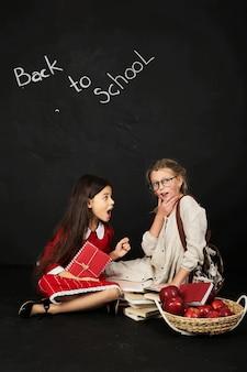 Две красивые подружки-школьницы сидят с книгами и корзиной яблок