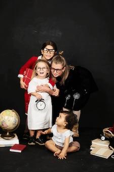 Три красивые школьницы из разных классиков и дошкольник на черном фоне