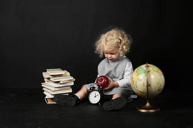 本、地球と時計、黒い背景に幸せな就学前の女の子