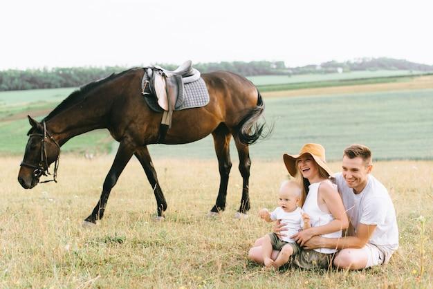 若い家族がこの分野で楽しんでいます。両親と馬を持つ子供