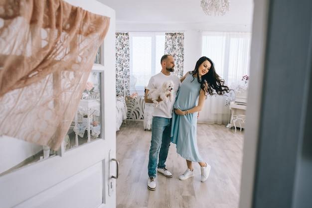 若いカップルが一緒に屋内で立っている赤ちゃんを期待して