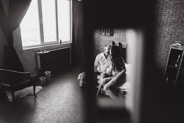 妊娠と人々のコンセプト - 自宅の窓に立っている彼の妊娠中の妻を抱いて幸せな男