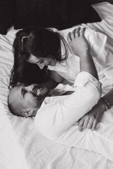 妊娠中のカップルは、赤ちゃんを待って、抱きしめるベッドでうそをつきます。