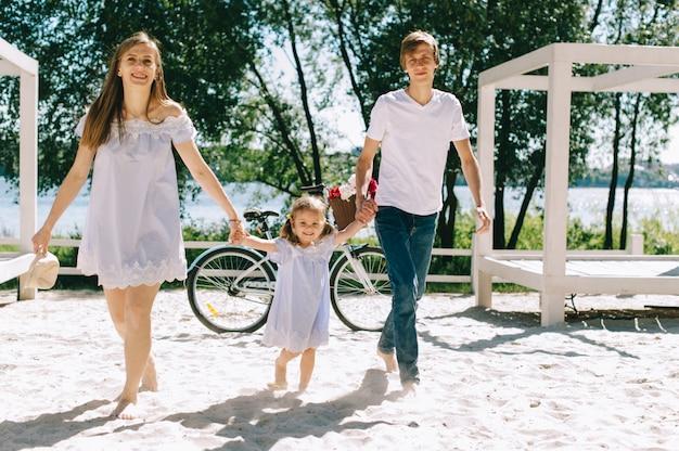 Счастливая семья на открытом воздухе проводить время вместе. отец, мать и дочь веселятся и бегают