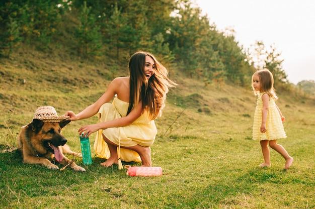 Мать гуляет со своей маленькой дочерью и их собакой