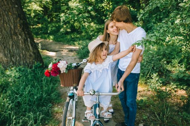 Счастливая молодая семья проводить время вместе снаружи. отец матери и их ребенок в зеленом парке