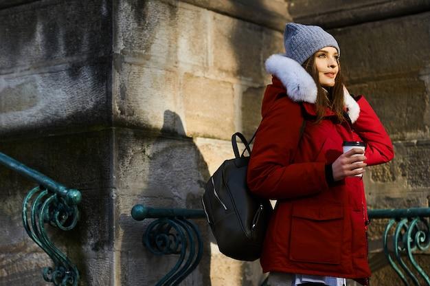 冬時間で路上でコーヒーを飲む若いおしゃれな女の子の肖像画