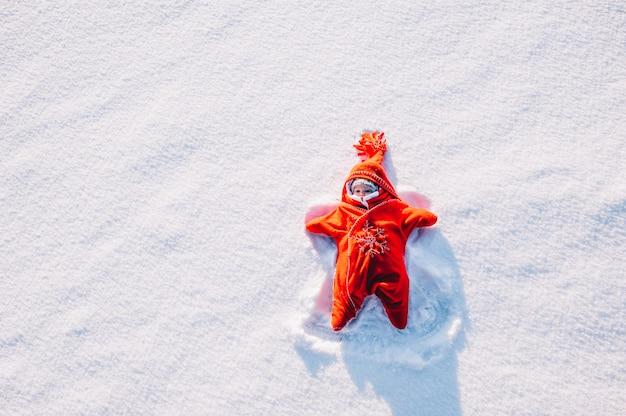 雪の上に横たわる少女