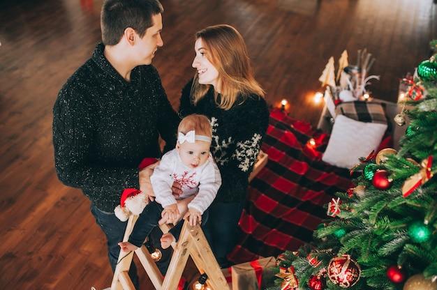 クリスマスツリーと暖炉のある家でクリスマス家族