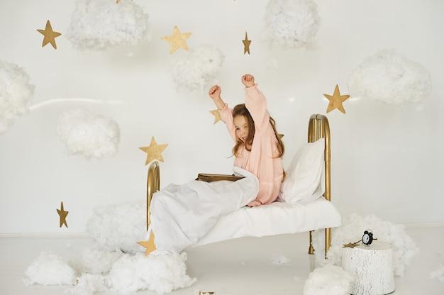 Маленькая принцесса с волшебной палочкой на кровати в облаке на белом фоне