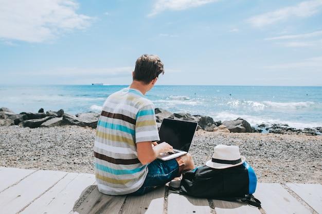 Красивый молодой парень фотограф работает с ноутбуком на пляже