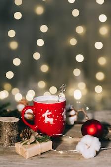 ライトの背景に赤のクリスマスコーヒーカップ