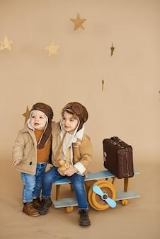 二人の兄弟は、おもちゃの飛行機とベージュ色の背景にスーツケースで遊んでいます。夢と旅行