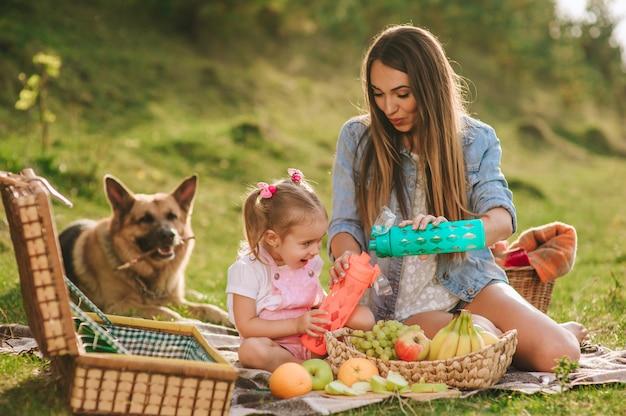 母と娘、犬と一緒にピクニックに