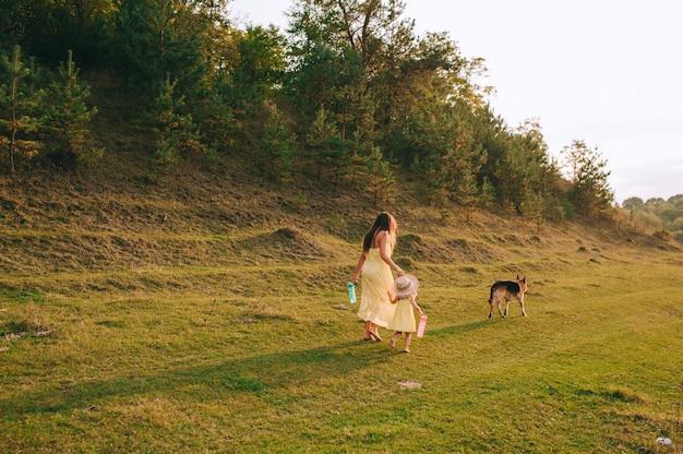 母は彼の幼い娘と彼らの犬と一緒に歩きます