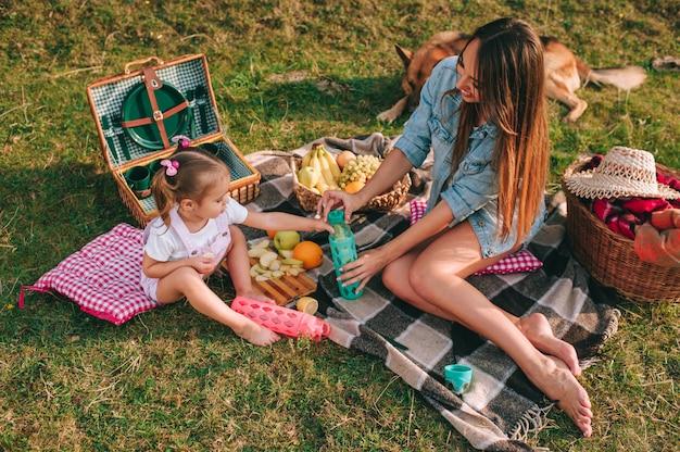 Мать и дочь на пикнике с собакой