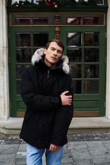 通りで冬の若いハンサムな男の子の肖像画