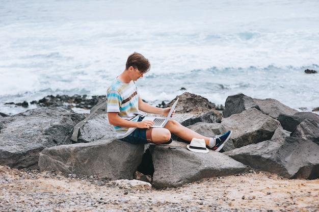 Деловой человек работает на пляже с ноутбуком