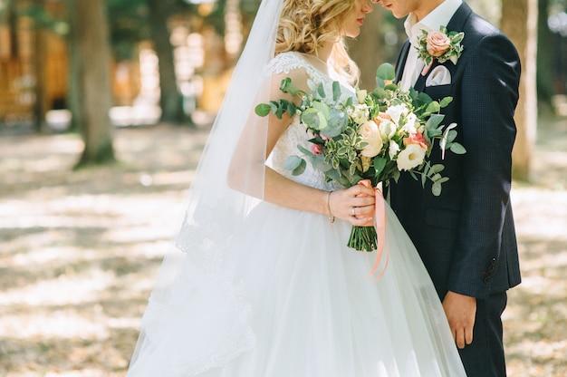 愛情のあるカップルのウェディングドレスに対してリングと手を取り合って