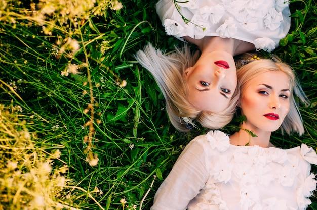 Две сестры-близнецы лежат на зеленой траве