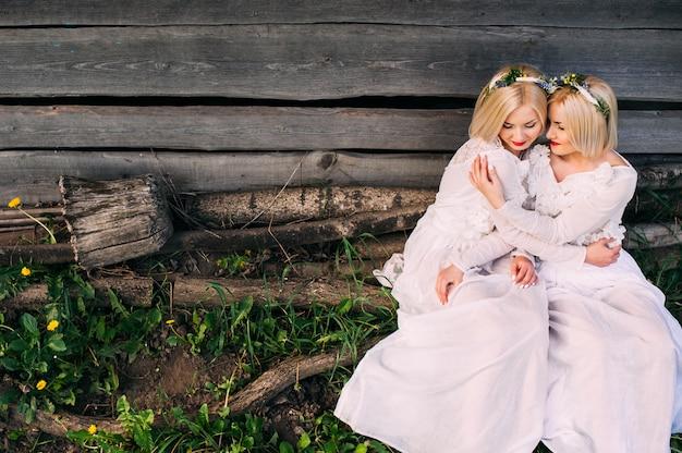 Две сестры сидят у деревянной стены