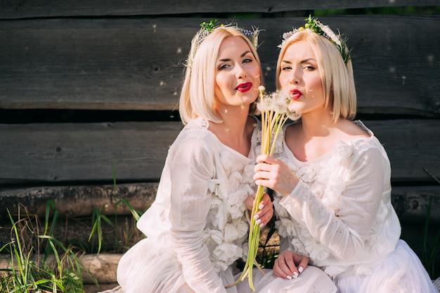 タンポポを吹く双子の姉妹