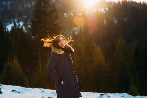 彼女の冬の暖かい服で美しい若い笑顔の女の子