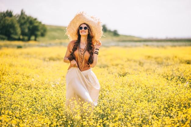 Романтическая девушка хиппи, стоя в поле. летом. стиль хиппи