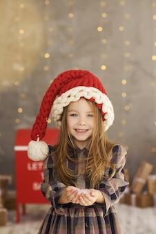 Портрет красивой маленькой девочки в рождественской шапке возле подарка на фоне