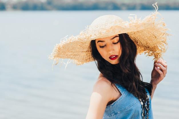大きな帽子の湖の上の美しい少女