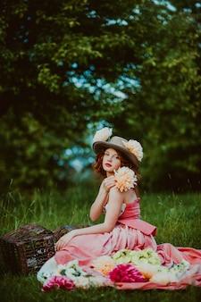 夏の日の屋外でウサギを持つ美しい女の子