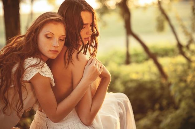 屋外で抱き合って二人の美しい女の子