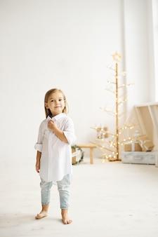 白い部屋の美しいドレスを着た木製のスツールに座っている美しい少女