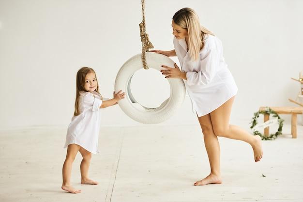 美しい妊娠中のお母さんは白い部屋のブランコに彼女の娘と遊ぶ