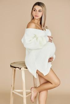 美しい妊娠中の女の子の肖像画は、ベージュ色の背景に白いセーターを着ています。