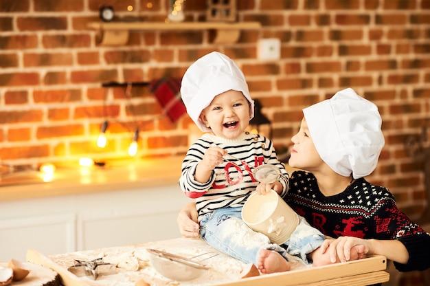 Детей готовят и играют с мукой и тестом на кухне