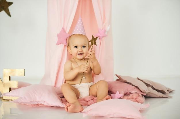 大きなケーキの近くに魔法の杖を持つピンクのテントの中の小さな赤ちゃん。誕生日のお祝いの概念