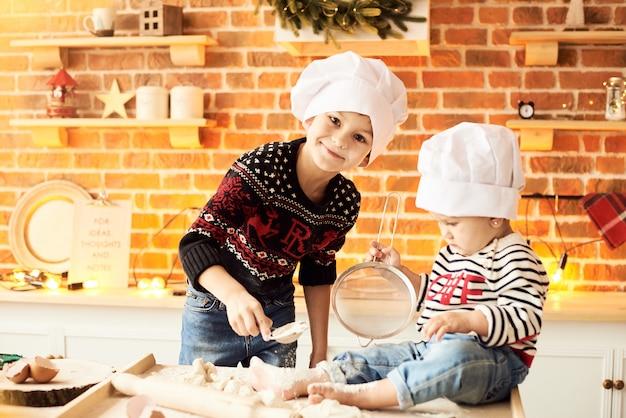 子供たちは台所で小麦粉と生地で調理され、遊ばれます