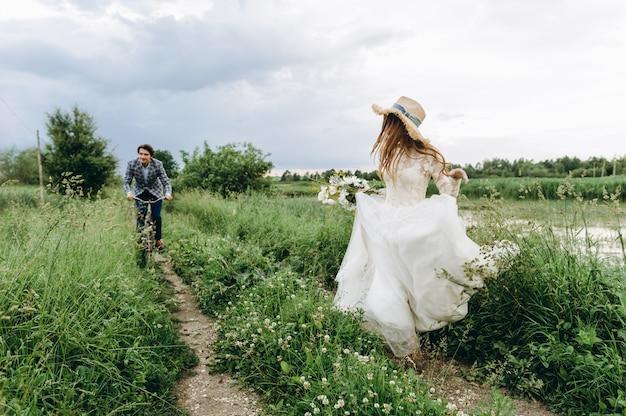 自転車でフィールドを歩いて美しい若いカップルの新郎新婦