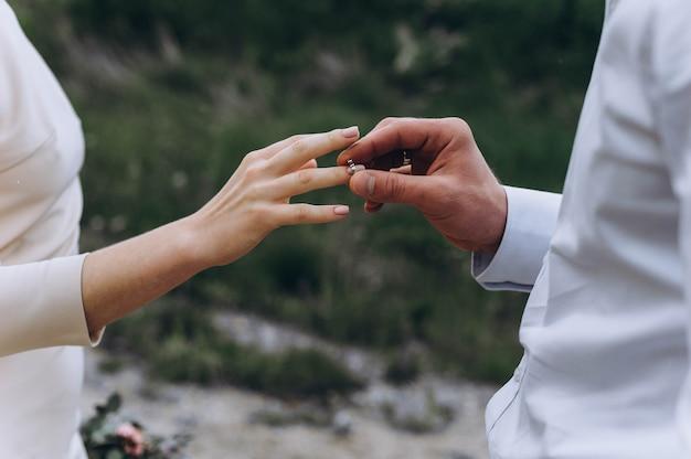 Жених надевает невесте обручальное кольцо на церемонии.